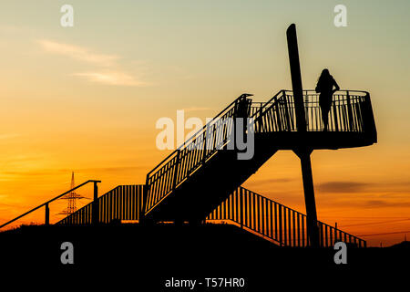 Herne, Germany. 22nd Apr, 2019. The silhouette of a woman and a viewing platform on the Pluto slagheap stand out against the sky of the setting sun. Credit: Marcel Kusch/dpa/Alamy Live News - Stock Image