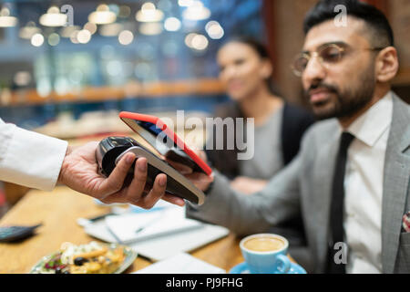 Businessman in cafe paying with smart phone contactless payment - Stock Image