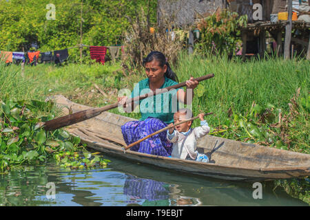 Woman with her child on a canoe in the middle of her floating vegetable garden - Stock Image