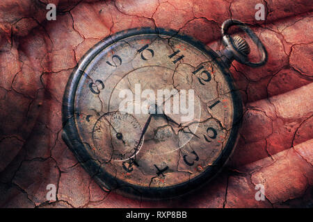 Digital composite of pocket watch in hand with cracked-earth background, emphasizing transience, the passing of time, aging, missed deadlines,  etc. - Stock Image