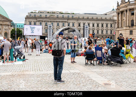 Berlin. Germany, 16th June 2019. Crowds gather at the Bebelplatz in front of St. Hedwig's Cathedral in Unter den Linden for the free annual Staatsoper für Alle Open Air Concert conducted by Daniel Barenboim. The Orchestra performed music by Johannes Brahms and Felix Mendelssohn Bartholdy on a temporary stage. The street was closed to traffic and Berliners and tourists flocked to the concert area with collapsible chairs and picnic hampers. Credit: Eden Breitz/Alamy - Stock Image