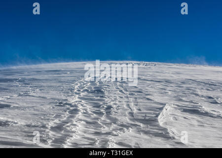 View of the wind storming and moving snow with a blue sky background, Passo Giau, Cortina d'Ampezzo, Dolomites, Italy - Stock Image