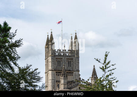 St Georges cross flag flying from the tower of  the Abbey Church of Saint Peter & Saint Paul (Bath Abbey) in the city of Bath viewed from the river - Stock Image