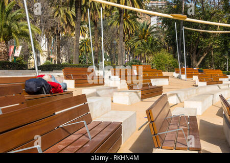 Homeless man sleeping on bench of outdoor theatre, Malaga, Andalusia, Spain. - Stock Image