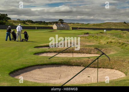Golf bunkers sand traps with rakes in a line on stands beside fairway - Stock Image