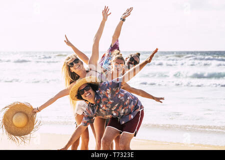 Happy cheerful group of young people friends having fun together in friendship at the beach with sea in background - tourism travel trousit concept wi - Stock Image