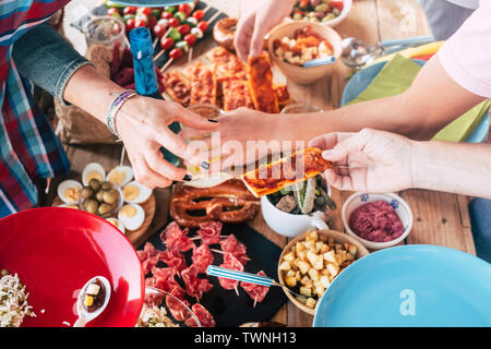 Above view of group of caucasian people eating food together - table full of food in background - friendship and together concept - enjoy friends at l - Stock Image