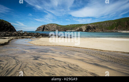 A stream of water flows across the sand and into Dalbeg Bay, Isle of Lewis, Outer Hebrides, Scotland, - Stock Image