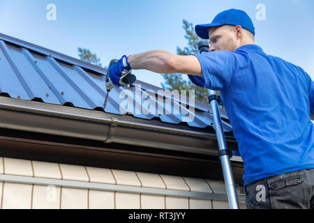 metal roofing - roofer working on the house roof - Stock Image