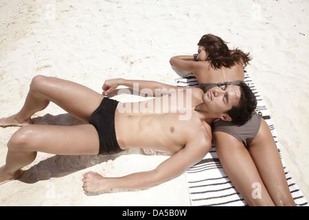 A couple sunbathing on a beach. - Stock Image