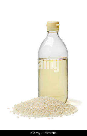 Bottle with traditional Japanese rice vinegar and a heap of rice isolated on white background - Stock Image