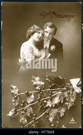 GERMANY - CIRCA 1915: A postcard printed in Germany, shows a couple in love. The inscription in German: Happy New - Stock Image