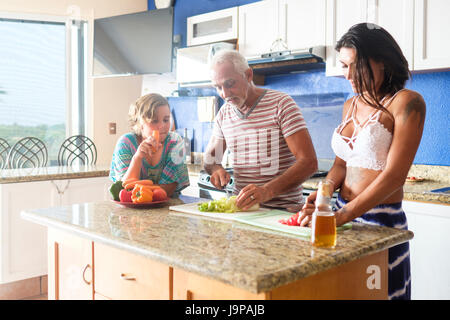 Older man cutting vegetables in the kitchen with young attractive woman, child watchin - Stock Image