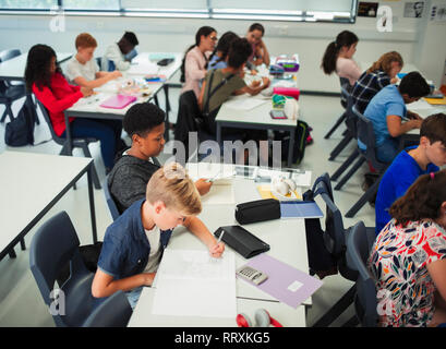 Junior high school students studying in classroom - Stock Image