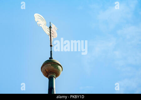 Weather vane on the top of a building showing the wind direction on a clear blue sky - Stock Image
