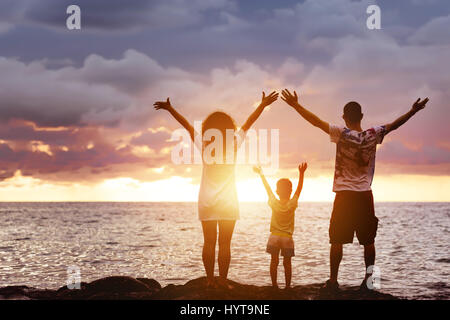 Happy family with son greetings sunset and sea - Stock Image