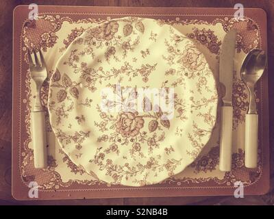 Old fashioned English China dinnerware with silverware - Stock Image