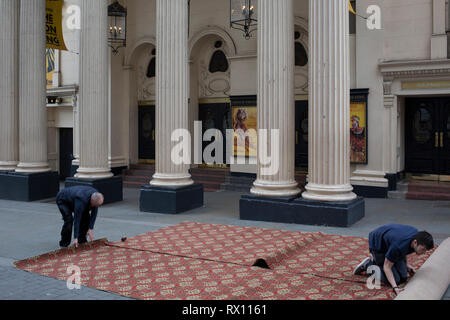 Carpet fitters trim a new carpet in the street for the interior of the Lyceum Theatre on Wellington Street, on 5th March 2019, in London, England. - Stock Image