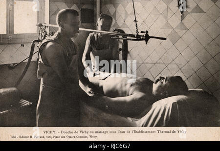 Vichy, France - Thermal Baths - Water Massage. The male attendant in the foreground appears to be checking his patient's pulse - one hopes the water jets did not have an adverse effect... - Stock Image