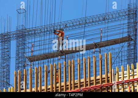 Construction worker on scaffolding on a high-rise building, San Jose, Province of San Jose, Costa Rica - Stock Image