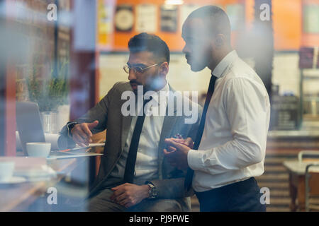 Businessmen working at laptop in cafe - Stock Image