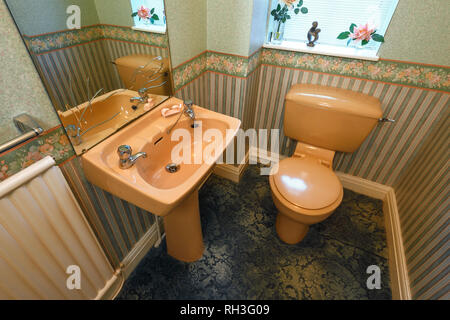 An old fashioned brown coloured suite in a downstairs toilet - Stock Image