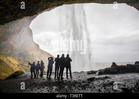 Seljalandsfoss waterfall, tourists taking picture under the waterfall - Stock Image