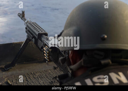 180825-N-AG490-0052  ATLANTIC OCEAN (Aug. 25, 2018) Aviation Boatswain's Mate (Equipment) Airman Apprentice Devorious Dibrelleferguson fires an M240 machine gun during a live-fire exercise on the fantail of the Nimitz-class aircraft carrier USS Abraham Lincoln (CVN 72). Abraham Lincoln is currently underway conducting carrier qualifications. (U.S. Navy photo by Mass Communication Specialist Seaman Maxwell Anderson/Released) - Stock Image
