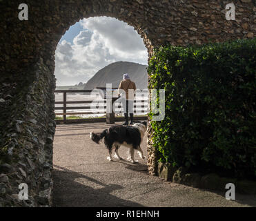 A woman looks out towards High Peak from Connaught Gardens in Sidmouth, Devon. - Stock Image