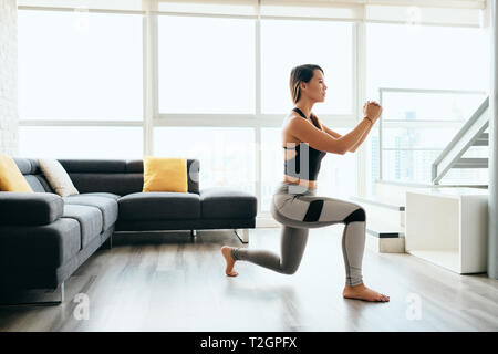 Fit young Pacific Islander woman training at home. Beautiful female athlete working out for wellbeing in domestic gym, training legs muscles doing lun - Stock Image