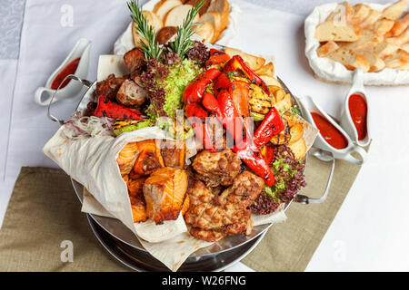 Mixed grill meat, fried vegetables and grilled salmon fish fillets decoration in warm dish. Assorted delicious grilled kebab served with herbs on plat - Stock Image