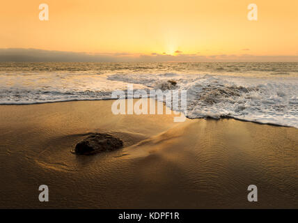 Sunset ocean wave is a serene scenic seascape on the beach with the bright sun setting on the ocean horizon as a - Stock Image