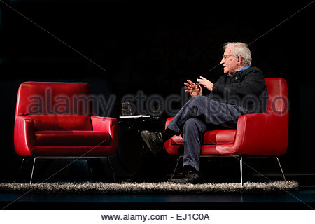 March 15th 2015 Noam Chomsky talking, speaking to empty red leather chair black background On Stage Audience University - Stock Image