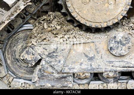 Mud clay encrusted earth moving tracks of a digger excavator machine in color with copy space area for gravel aggregate - Stock Image