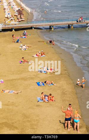 Tourists sun bathing on Finikoudes beach, Larnaca, Cyprus October 2018 - Stock Image