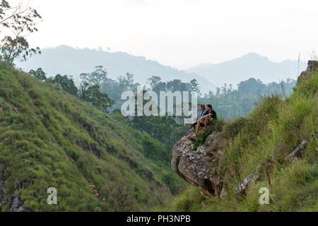 Travel concept. Couple sitting on top of Small Adams peak near Ella, Sri Lanka - Stock Image