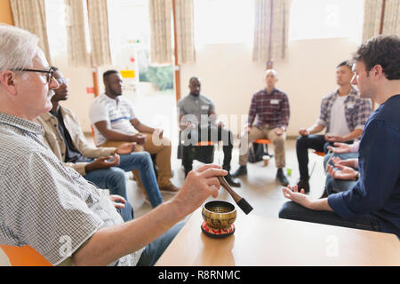 Man using singing bowl in meditation group - Stock Image