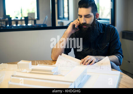 Architect looking at blueprints and talking on cell phone in office - Stock Image