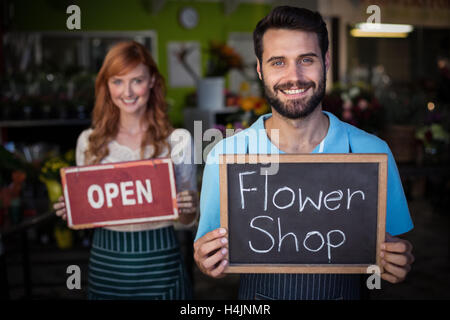 Man holding slate with flower shop sign and woman holding open signboard - Stock Image