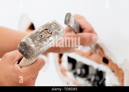 closeup of caucasian man making a hole in a plastered brick wall using a hammer and a cold chisel - Stock Image