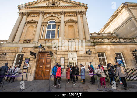 A group of Chinese tourists queue outside the entrance to the historic Pump Rooms in Bath on a sunny day in winter waiting for the doors to open - Stock Image