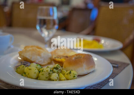 A plate with a simple hotel breakfast consisting of potatoes and bread - Stock Image