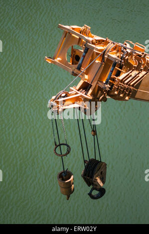 Crane and machinery suspended over water - Stock Image