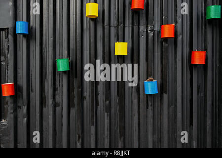 many painted colorful empty cans reused as flower pots, mounted to the black metal wall, environment friendly and creative idea - Stock Image