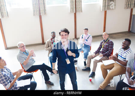 Men clapping for speaker in group therapy - Stock Image