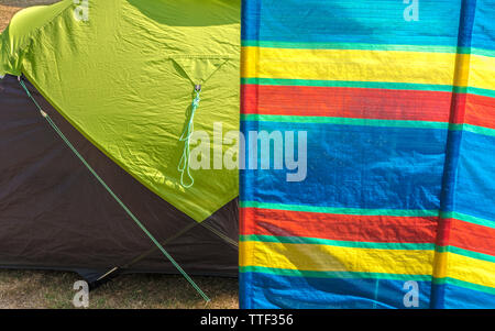 A colourful striped windbreak providing shelter for the small tent alongside, in the summer sunshine. England, UK. - Stock Image