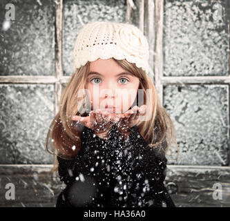 A young child is blowing white snowflakes in a winter background scene for a holiday christmas or season concept. - Stock Image