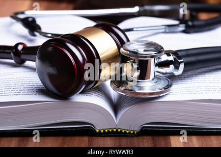 Close-up Of Stethoscope And Mallet Over Opened Law Book On Wooden Desk - Stock Image