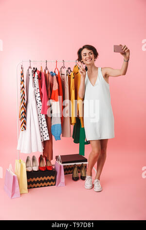 Image of a beautiful happy woman stylist posing isolated over pink wall background near a lot of clothes take a selfie by mobile phone. - Stock Image