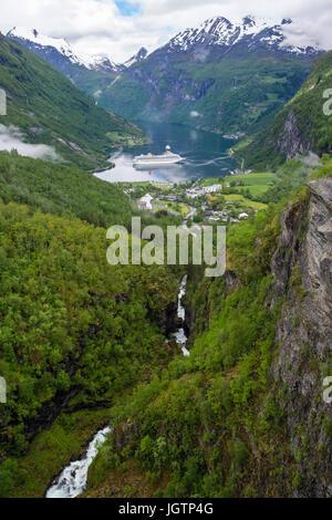 Scenic view above Geirangelva river gorge to village at end of Geirangerfjorden fjord in summer. Geiranger, Sunnmøre - Stock Image